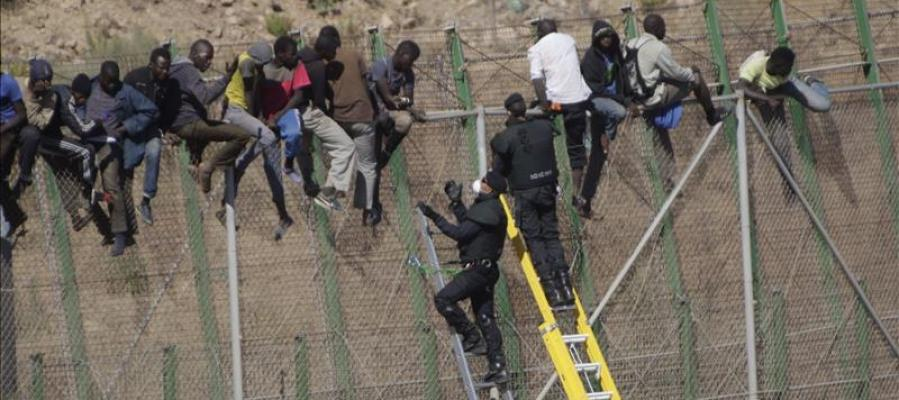 Inmigrantes sobre la valla de Melilla