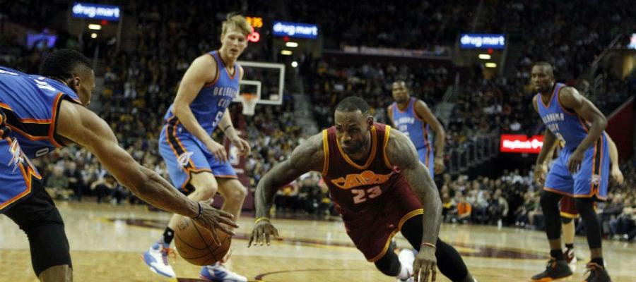 LeBron James trata de cazar un balón ante los jugadores de Oklahoma