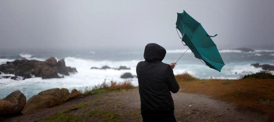 Un hombre ve como el viento le dobla el paraguas en A Coruña