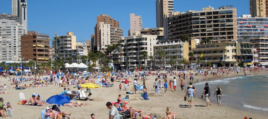 Playa con apartamentos al fondo.