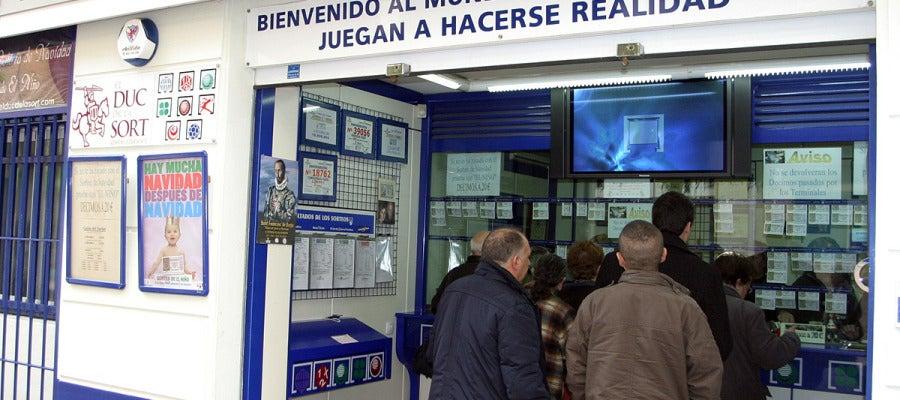 Varias personas comprando lotería en una administración.