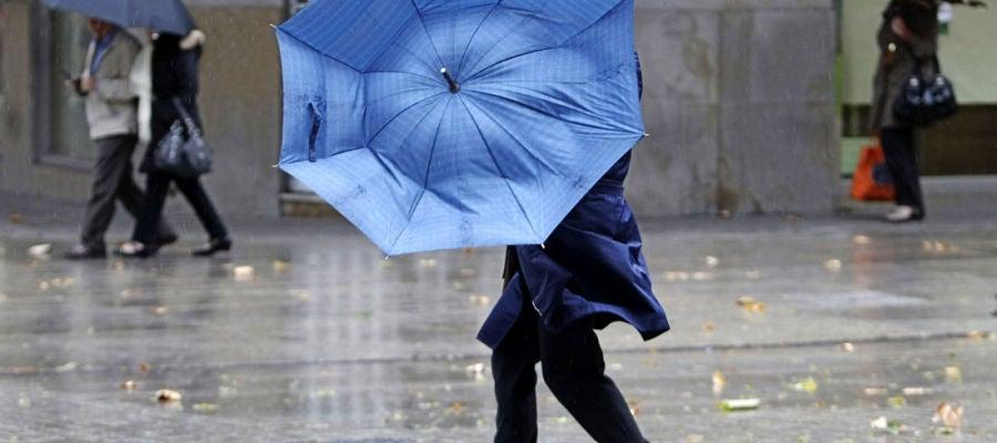 Una mujer se protege de la lluvia y el viento