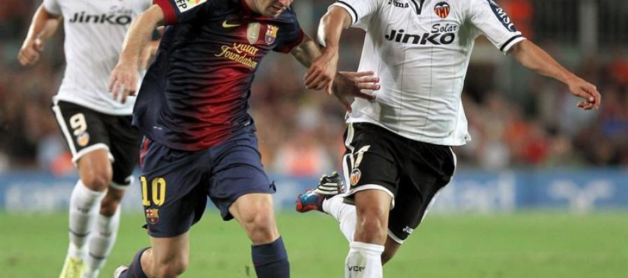 El delantero argentino del FC Barcelona Leo Messi se marcha del centrocampista mexicano del Valencia CF Andrés Guardado, en presencia del delantero Roberto Soldado.