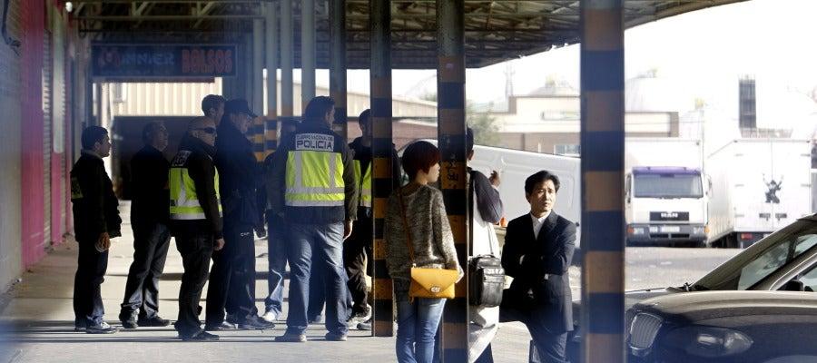 Agentes de la Policía Nacional y ciudadanos chinos durante el registro a negocios en el polígono industrial Cobo Calleja, de Fuenlabrada