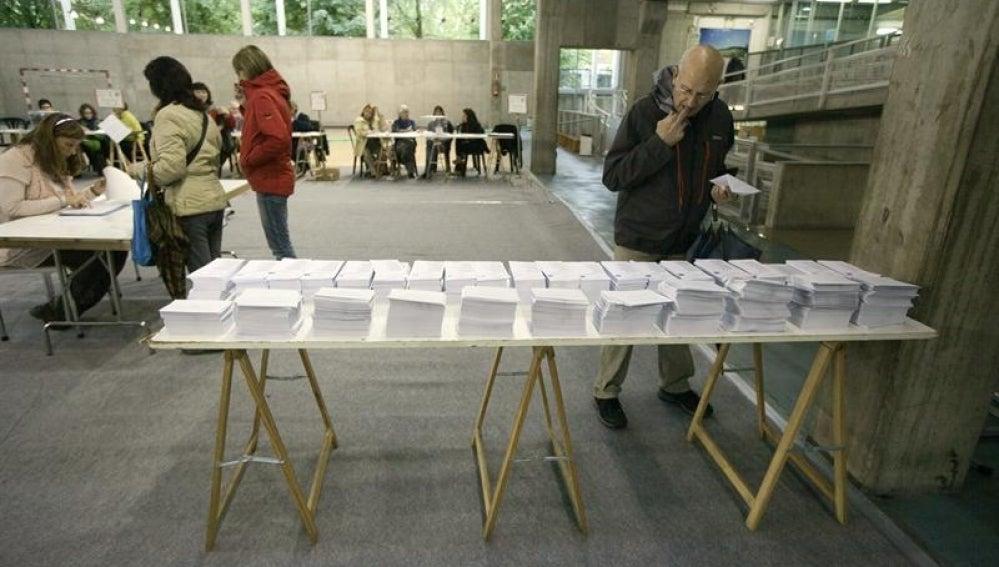 Un votante elige su papeleta en un colegio electoral situado en un centro cívico de Vitoria.