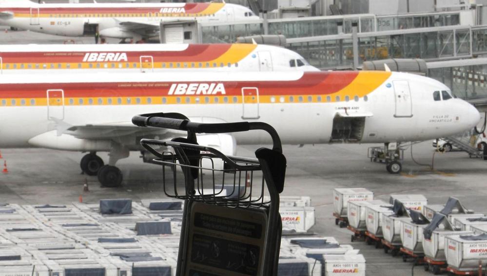 Un carrito de equipajes ante varios aviones de Iberia