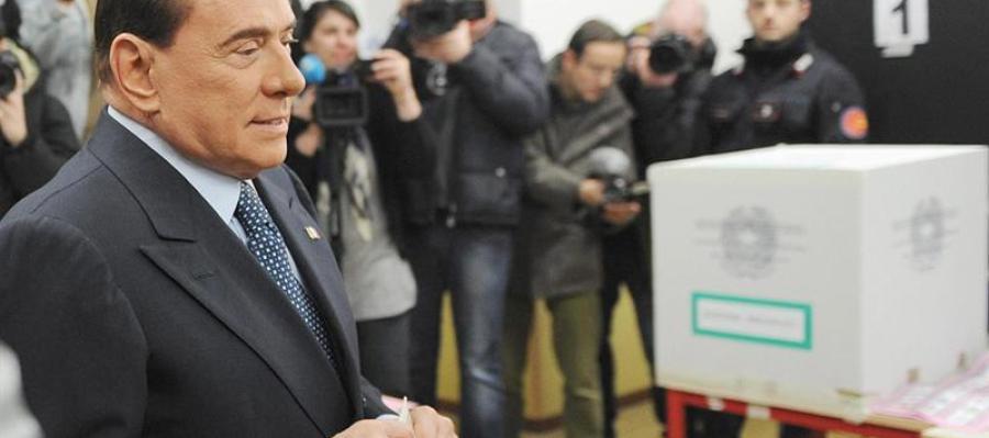 Berlusconi inserta su voto en urna urna electoral.