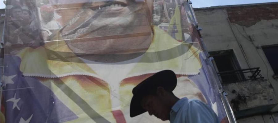 Un hombre pasa frente a una imagen del presidente de Venezuela Hugo Chávez