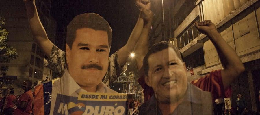 Venezolanos con carteles de Maduro y Chávez