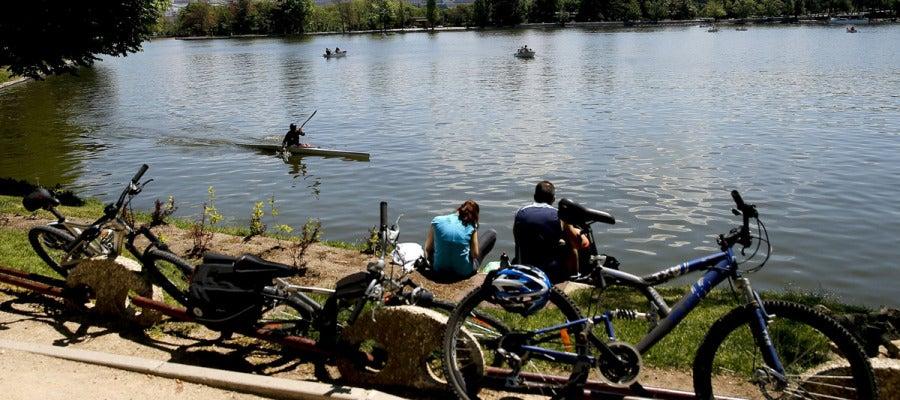 Varias personas descansan junto al lago de la Casa de Campo