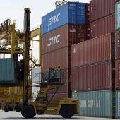 Una grúa transporta un contenedor en un puerto.