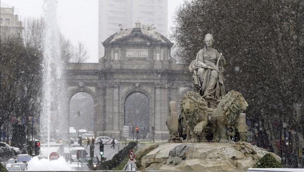 Vista de la Cibeles con la Puerta de Alcalá al fondo, bajo la nieve que cae en Madrid