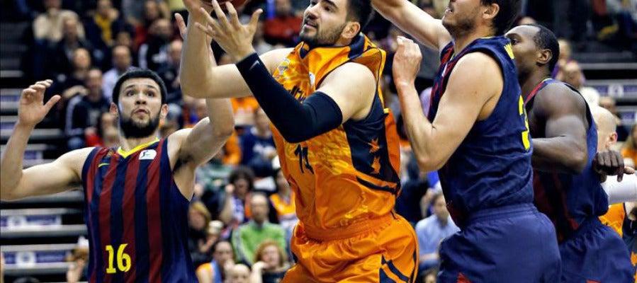 El ala pivot del Valencia Basket Bojan Dubljevic intenta superar la defensa del alero del Barcelona Bostjan Nachbar y del alero griego Kostas Papanikolau