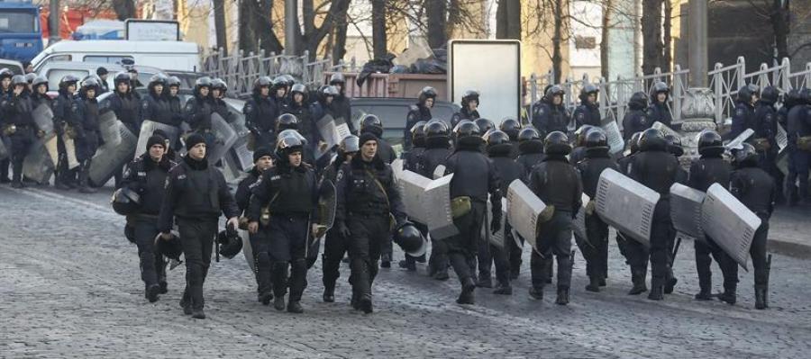 Decenas de policías antidisturbios vigilan la calle Grushevskogo, frente a una barricada de manifestantes en Kiev.