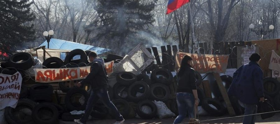 Ucranianos pasan ante una barricada de un edificio ocupado.