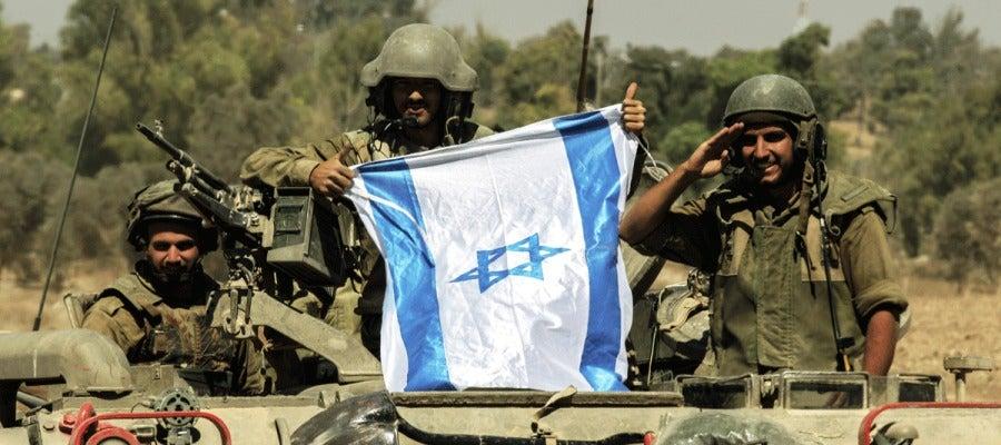 Soldados israelís portan una bandera de Israel sobre un tanque