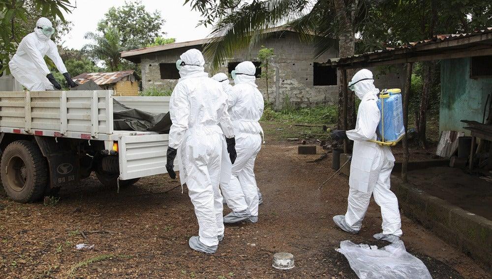 Varios enfermeros liberianos mientras rocían con desinfectante una casa