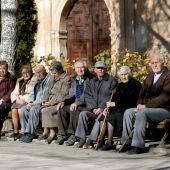 Varios ancianos toman el sol en unos bancos de Olmeda de la Cuesta, Cuenca