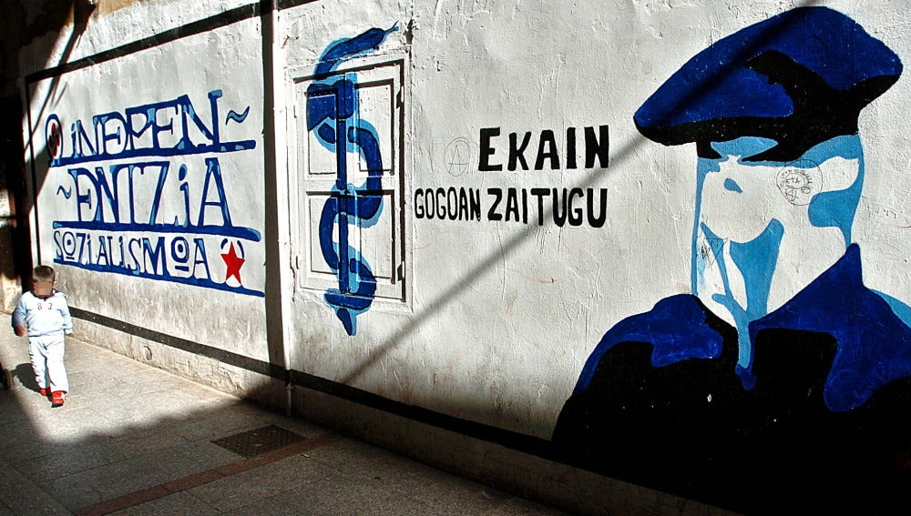 Un niño pasa junto a un mural que representa a un encapuchado junto al anagrama de ETA