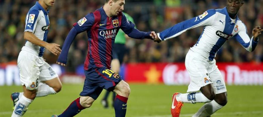 Messi conduce el balón junto a dos jugadores del Espanyol