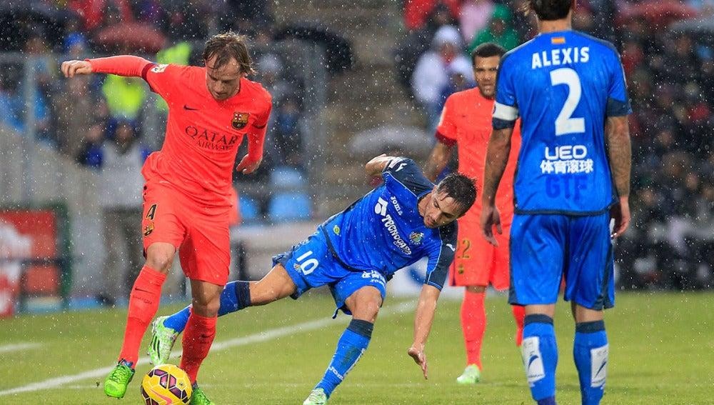 Rakitic pelea por un balón bajo la lluvia