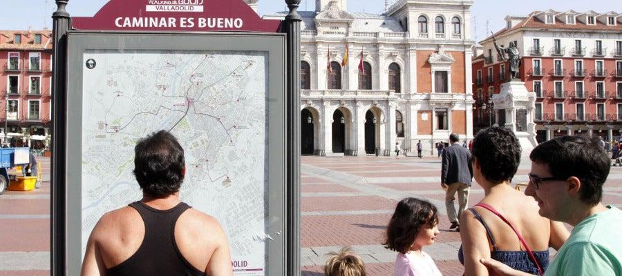 Una familia de turistas observa el panel informativo de las rutas 'Caminar es bueno' en la Plaza Mayor de Valladolid