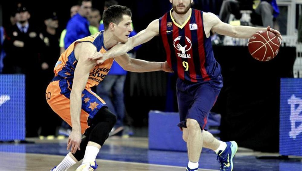 Marcelinho Huertas intenta superar la defensa del base serbio del Valencia, Nemanja Nedovic