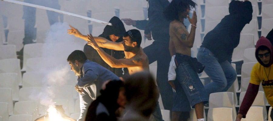 Seguidores del Panathinaikos lanzando objetos desde la grada
