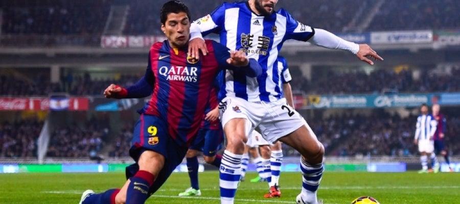 Luis Suárez lucha por un balón ante De la Bella