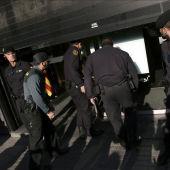 Agentes ante la fachada de la sede de CDC en Barcelona que esta siendo registrada