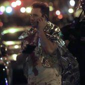 Un hombre ensangrentado habla por teléfono junto a un policía en el exterior de la discoteca Bataclan en París