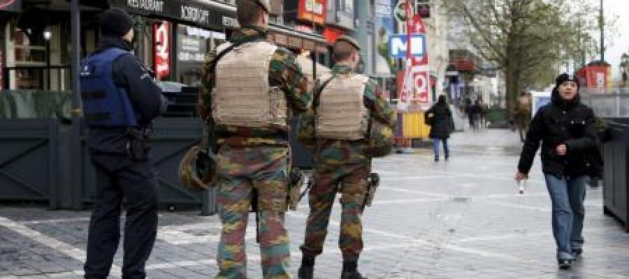 oficial de la policía belga junto a soldados patrullando la zona comercial en Bruselas