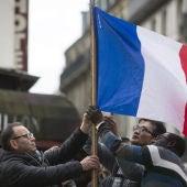 Varias personas sujetan una bandera de Francia