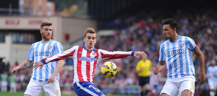 Griezmann controla el balón ante los defensores del Málaga