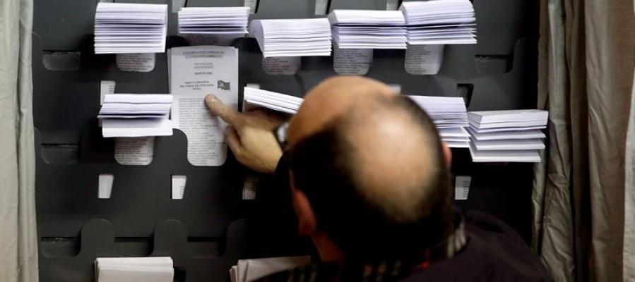 Un hombre elige las papeletas para las elecciones generales
