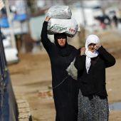 Refugiados sirios trasladan bolsas de alimentos en el paso fronterizo de Öncüpinar, en Kilis, Turquía