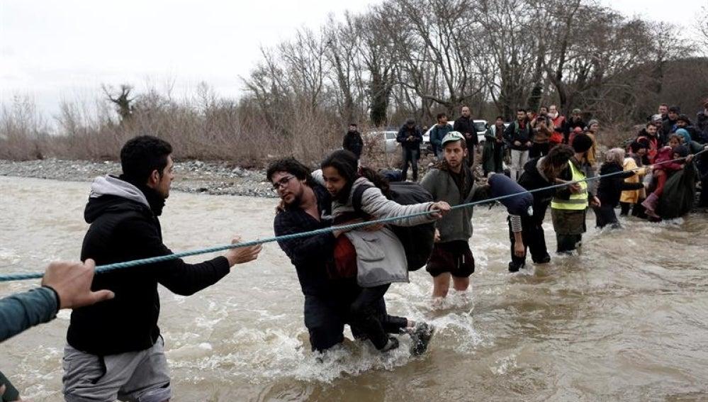 Refugiados usan una cuerda para cruzar el río en la frontera con Macedonia