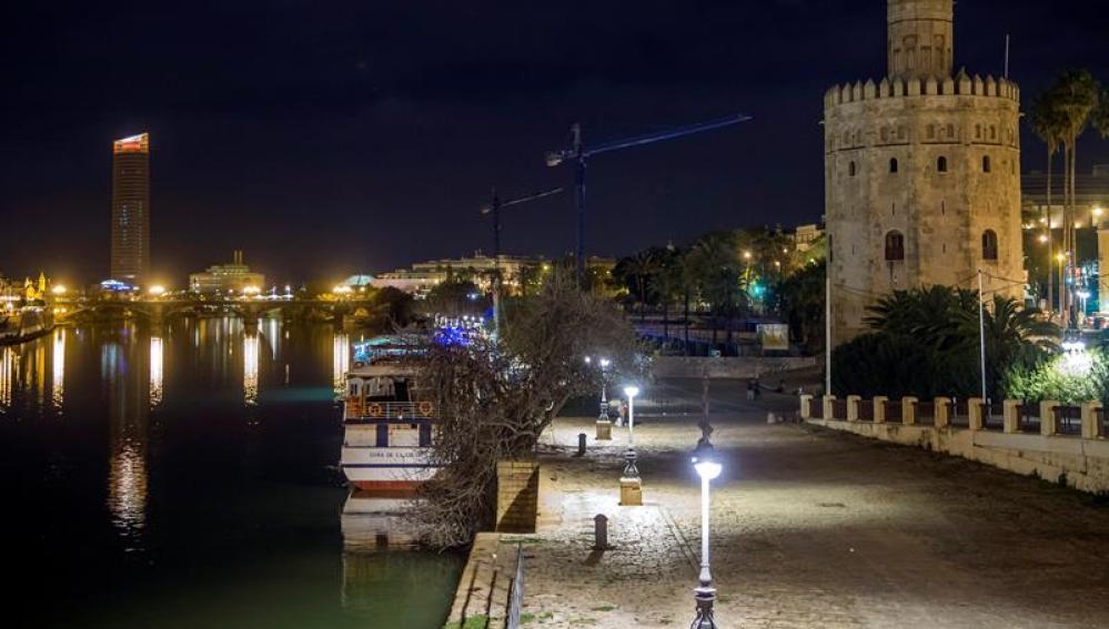 La sevillana Torre del Oro y el Puente de Triana durante el apagón de luces que se ha realizado con motivo de 'La Hora del Planeta'