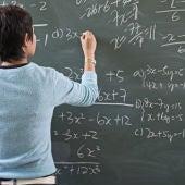 Imagen de una profesora escribiendo en la pizarra