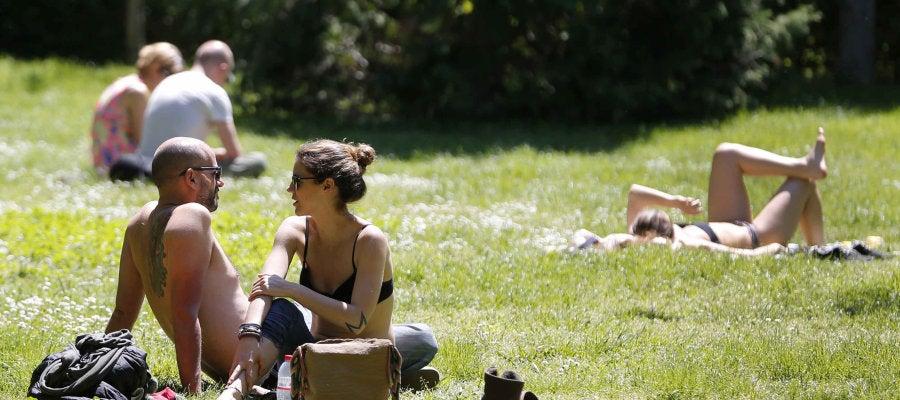 Varias personas toman el sol en el Parque del Retiro