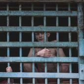 Dos prisioneros miran a través de los barrotes de su celda en la prisión