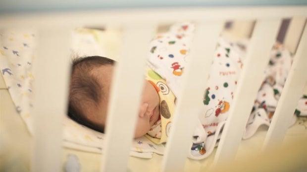 Un bebé recién nacido duerme en una cuna