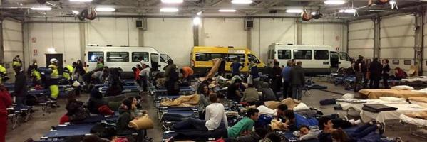 Decenas de personas evacuadas por los terremotos, pasan la noche en un hangar de autobuses convertido en refugio temporal en Italia