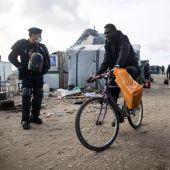Agentes de policía galos observan a varios migrantes que son evacuados del campamento de Calais
