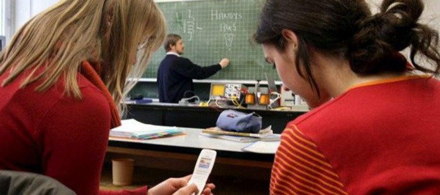 Dos alumnas utilizan sus teléfonos durante una clase