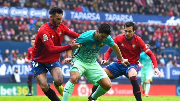 Luis Suárez intenta retener el balón ante la defensa de Osasuna