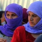 Varias mujeres hacen cola para coger comida en un campo de refugiados de Kurdistán