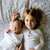 Niña y bebé en cama