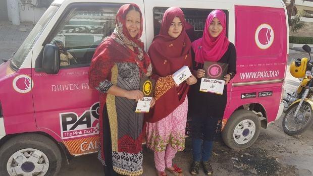 Tres mujeres pakistaníes posan junto a uno de los taxis rosas que circulan para proteger a las mujeres del acoso