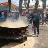 Dos de los cocineros del arroz con costra junto al perol metálico en el que se ha preparado el plato